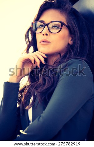 young elegant woman with eyeglasses portrait, outdoor, retro colors - stock photo