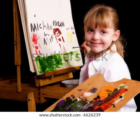 Young elementary girl holding a palette while painting on an easel.
