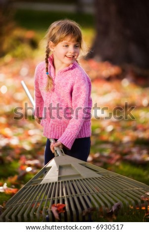 Young elementary girl raking leaves.