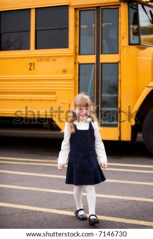Young elementary girl walking away from the school bus.