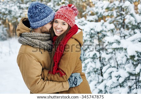 Young embracing couple looking at camera in park - stock photo