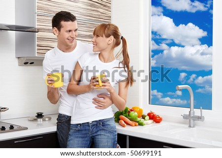 Young embracing couple with yellow mugs at kitchen - stock photo