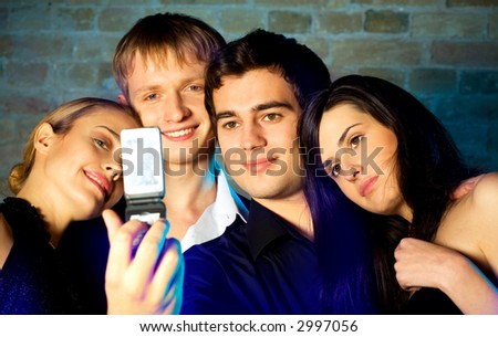 Young embracing smiling people taking photograph by cellphone and posing at celebration or night party