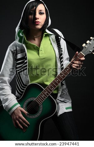young emo girl with guitar on black background - stock photo