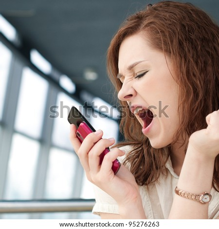 Young emotional business woman with phone at cafe - stock photo
