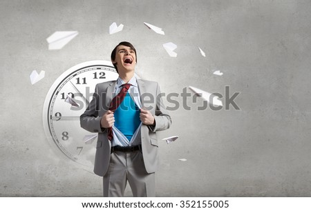 Young emotional businessman acting like super hero and tearing his shirt off - stock photo