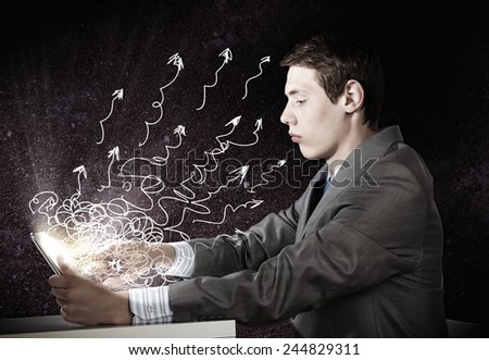 Young emotional businessman looking in tablet pc - stock photo