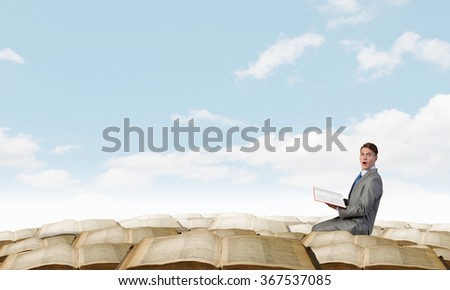 Young emotional businessman with opened book in hand