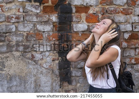 Young emotional girl enjoying music with headphones on the brick wall background. - stock photo