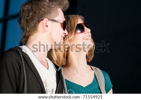Young emotional happy teenage couple playing on grass in city park - stock photo