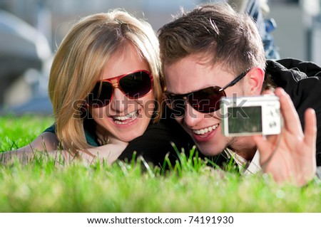 Young emotional happy teenage couple taking picture on grass in city park