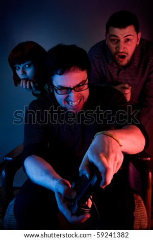 Young emotional man playing video games, two scared persons are hiding behind him