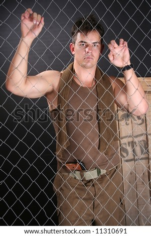 Young emotional soldier behind fence with weapon - stock photo