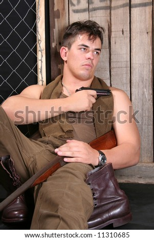 Young emotional soldier with weapons in studio - stock photo