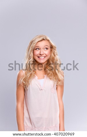 Young emotional woman, isolated on gray background - stock photo