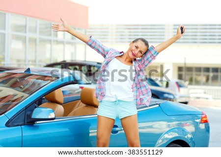 Young emotional woman standing near a convertible with the keys in her hand - concept of buying a used car or a rental car