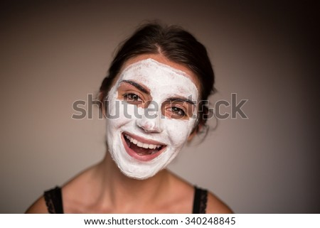 Young emotional woman with facial mask