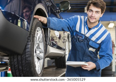 Young employee of a automotive workshop inspects a car together with his checklist - stock photo