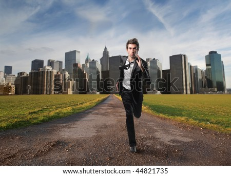 young employee running away from modern city - stock photo