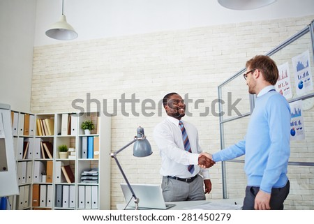 Young employer congratulating newly hired man - stock photo