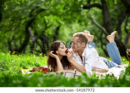 Young enamoured couple on picnic in wood - stock photo