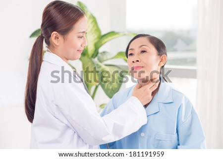 Young endocrinologist checking goiter to a senior patient  - stock photo
