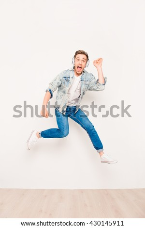 Young energetic crazy man listening music and jumping