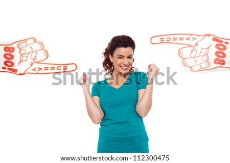 Young energetic female showing her true fan spirit with large foam hands pointing her from both the sides - stock photo