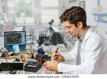Young energetic male tech or engineer repairs electronic equipment in research facility. Shallow DOF, focus on the face of the worker. - stock photo