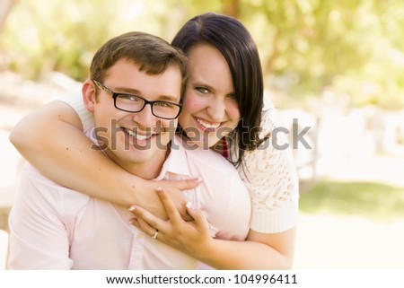 Young Engaged Couple Sharing a Moment in the Park - stock photo
