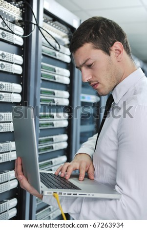 young engeneer business man with thin modern aluminium laptop in network server room - stock photo