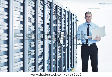 young engeneer business man with thin modern aluminium laptop in network server room