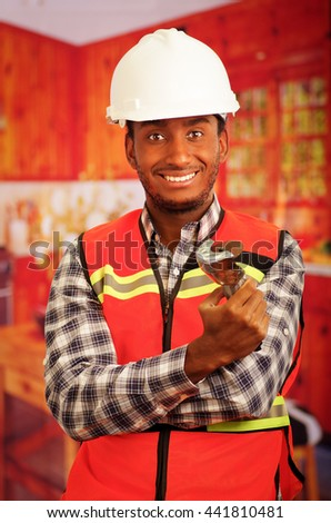 Young engineer carpenter wearing helmet, square pattern flanel shirt with red safety vest, holding small handheld electric saw smiling to camera - stock photo