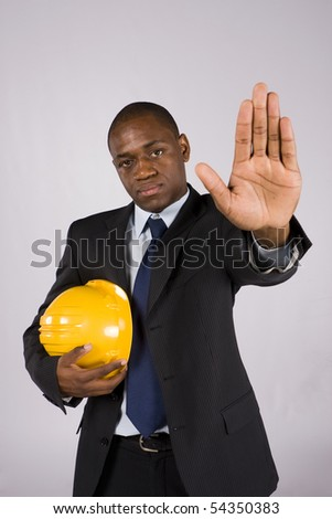 Young engineer holding a yellow helmet ordering to stop with his hand - stock photo