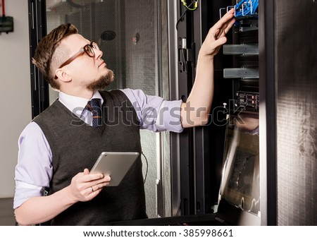 Young engineer in a datacenter - stock photo