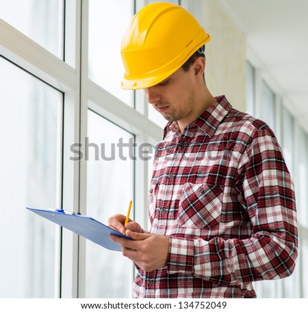young engineer in a helmet signed a contract - stock photo