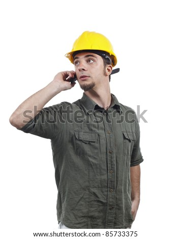 Young engineer in helmet talking on a mobile phone