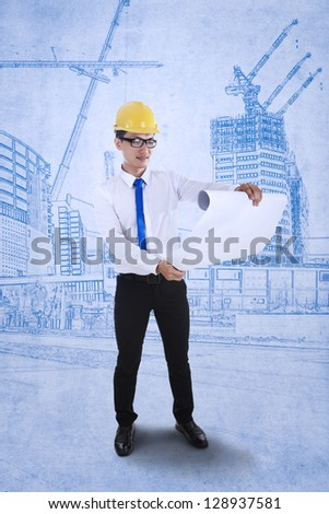 Young engineer is reviewing a plan over blueprints background - stock photo