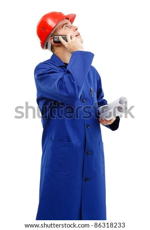 Young engineer looking up to copy space while talking on the phone, holding plan rolls in his hand - stock photo