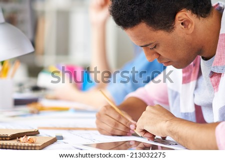 Young engineer making sketch of construction - stock photo