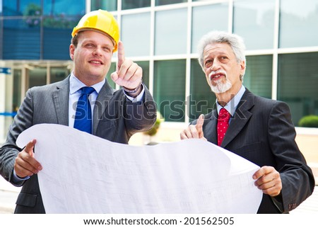 young engineer showing something to his partner at building site  - stock photo