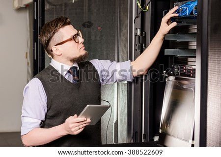 Young engineer wearing glasses in a datacenter - stock photo