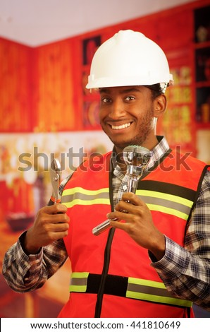 Young engineer wearing square pattern flanel shirt with red safety vest, holding showerhead and pliars smiling to camera - stock photo