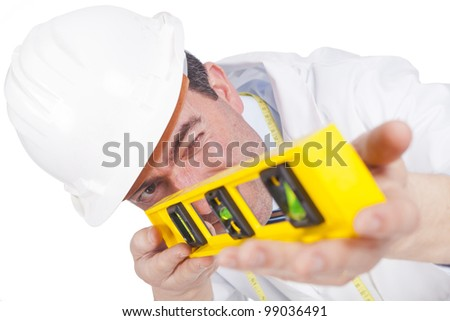 young engineer with a helmet on paying attention and using a level (focus on the face) - stock photo
