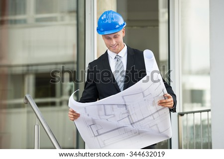 Young Engineer With Hard Hat Holding Blueprint In His Hands - stock photo