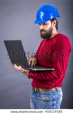 Young engineer with hardhat standing while working on his laptop over gray background - stock photo