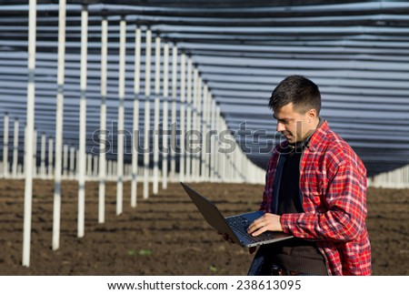 Young engineer with laptop standing on soil with white steel columns