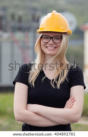 Young engineer with yellow helmet near his workplace - stock photo