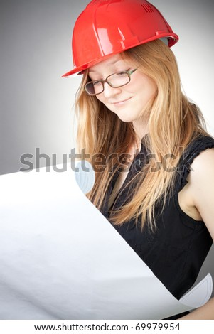Young engineer woman in helmet with blueprint, with grey background - stock photo