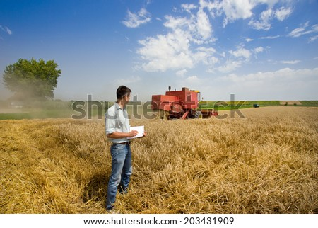 Young engineer writing notes in book on wheat field, combine harvester in background  - stock photo